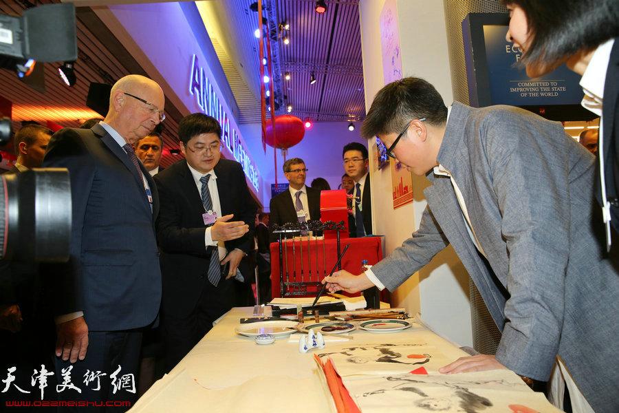 """图为李旭飞在瑞士2016年达沃斯世界经济论坛""""天津之夜""""现场创作金猴献寿为主题的中国画。"""