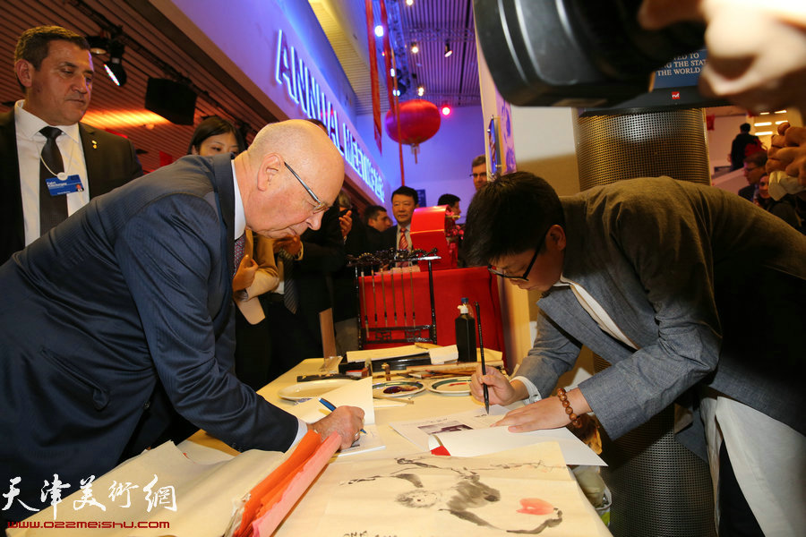 """图为施瓦布、 李旭飞在瑞士2016年达沃斯世界经济论坛""""天津之夜""""现场相互签名赠书。"""