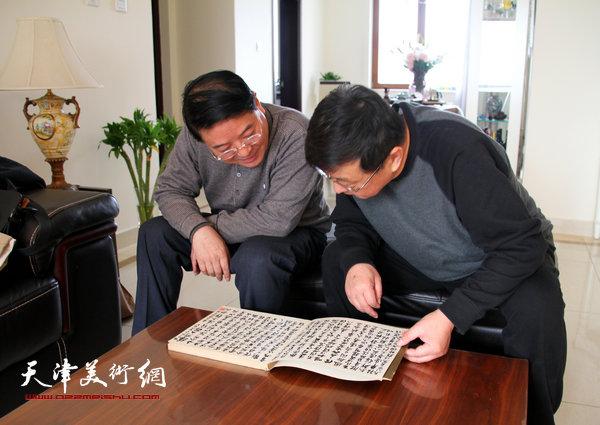爱新觉罗·载庸与刘学仁观赏书法作品。