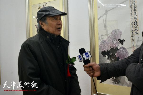 图为郭书仁在画展现场接受媒体采访。