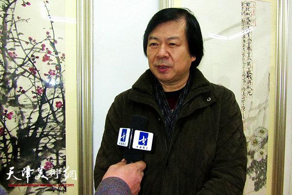图为史振岭在画展现场接受媒体采访。