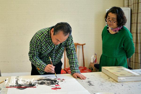 李寅虎在创作。右为乾庄书画院院长肖英隽。