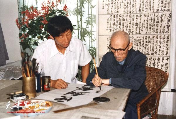 曹恩祥在观摩梁崎先生写书法。
