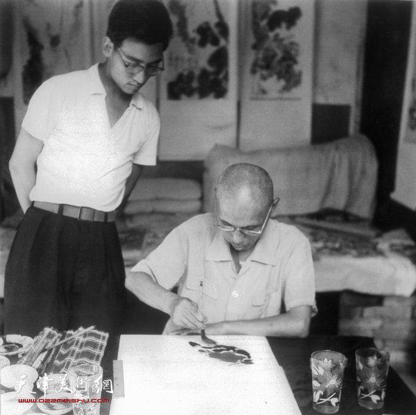 1964年夏日,梁崎先生于家中绘画,左立者为天津已故著名花鸟画家史如源。