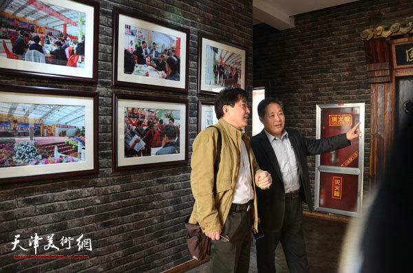 蓬莱仙山书画院刘总向王文元介绍书画院情况