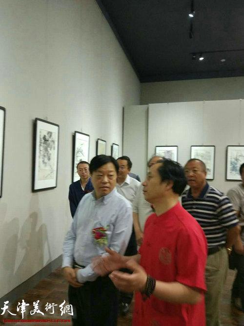 张大功与领导在画展现场观赏作品