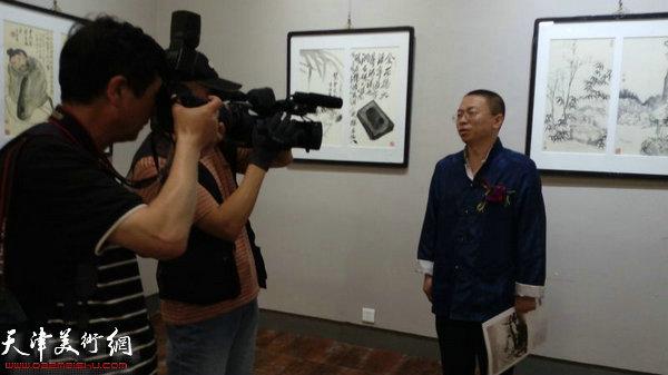 主办方负责人在画展现场接受媒体采访