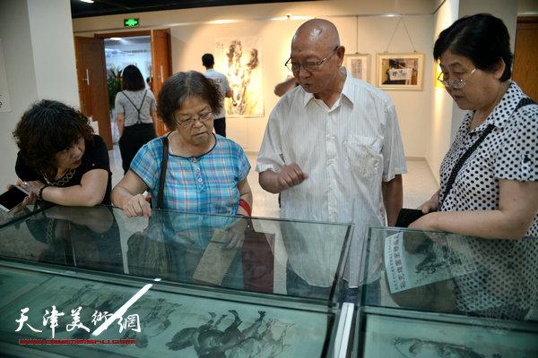 孙克维与书画爱好者在观赏展品。