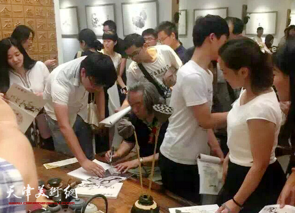 霍春阳在画展现场位观众签名。