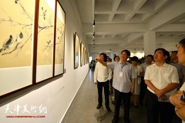 张吉福、李尔山等观赏展出的作品。