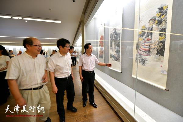 王宏江、刘志永、王宝贵在观看展出的作品。
