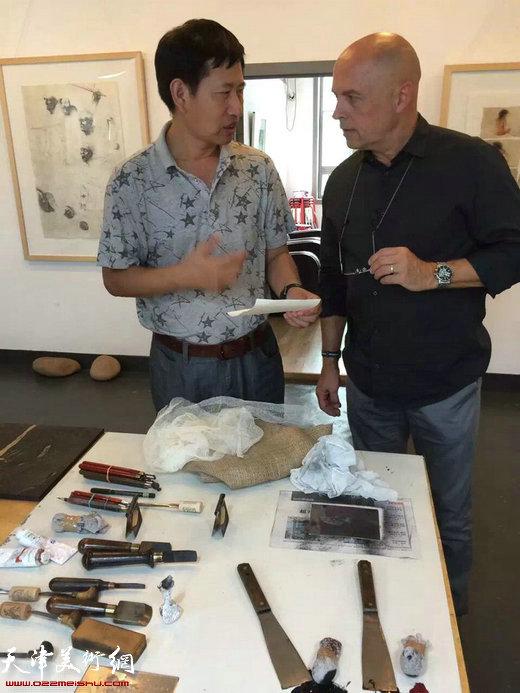 伊日·布拉兹达与天津师范大学教授、西青区美协主席李桂金在展览现场交流版画艺术。