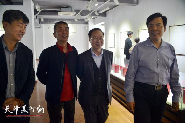李耀进、邓国源、庞黎明在观赏展出的作品。