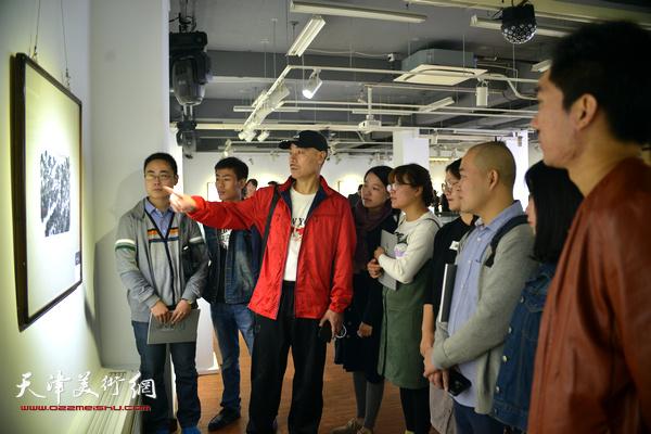 王慧智和他的学生们在赏析展出的作品。