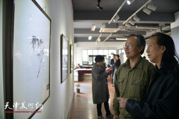 陈福春、周世麟在观赏展出的作品。