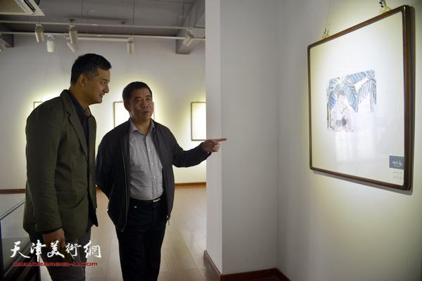 杨维民、窦良羽在观赏展出的作品。