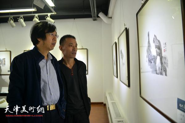 路洪明、段为民在观赏展出的作品。