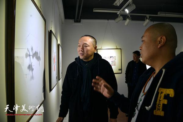 薛明在观赏展出的作品。