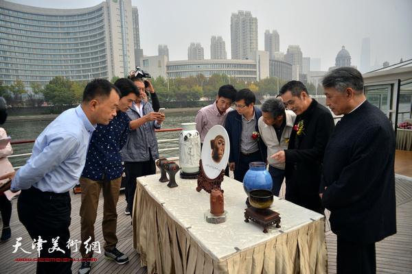 李梓源与来宾在海河一号上观赏展品。