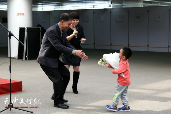 李建平老师的孙子代表全家人向爷爷开画展献花。