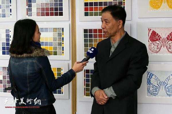 李建平老师在画展上接受媒体采访。