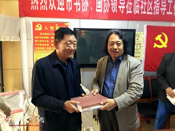 天津画院院长贾广健向龙湾书画院院长张玉凤赠送专业画册。