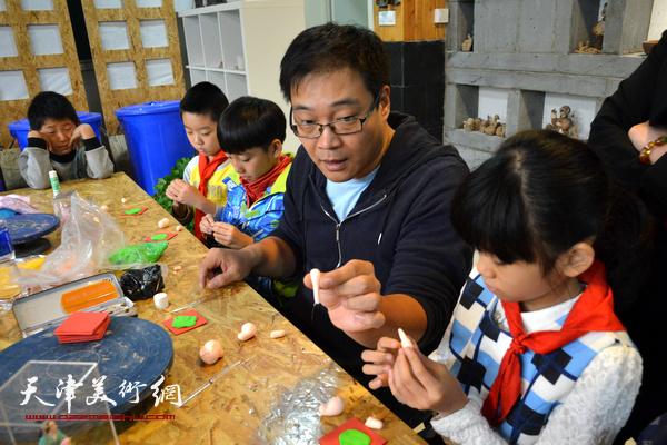 津派面塑传承人张亚杰教小学生们捏小猪。