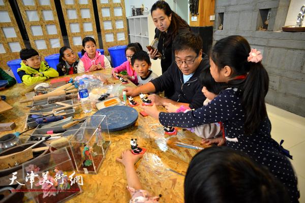 津派面塑传承人张亚杰教小学生们捏大熊猫。