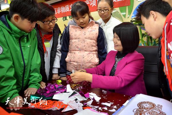 广东汕头高级工艺美术大师许遵英演示剪纸技艺。