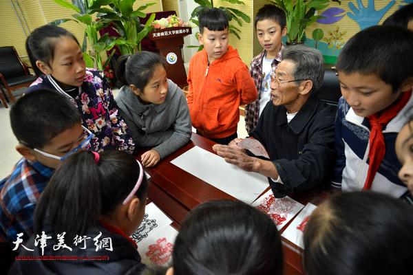 山东高密范氏剪纸第二代传人范祚信演示剪纸技艺。