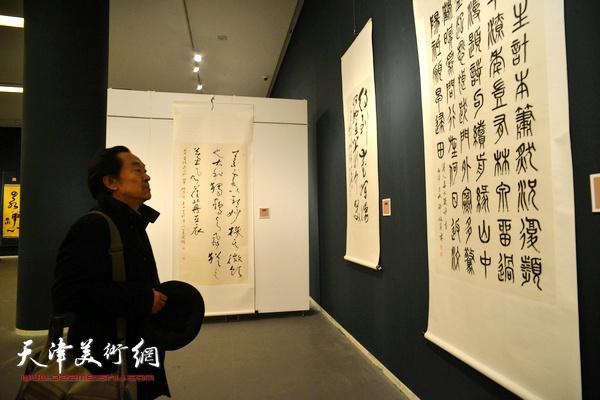 王全聚在观看展出的作品。