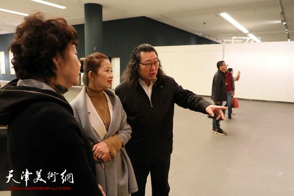 宋莉民、朱立、邓英彪在观看展出的作品。