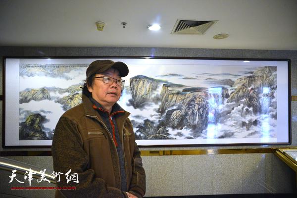 董振涛在巨幅山水画作《苍峰云瀑》前。