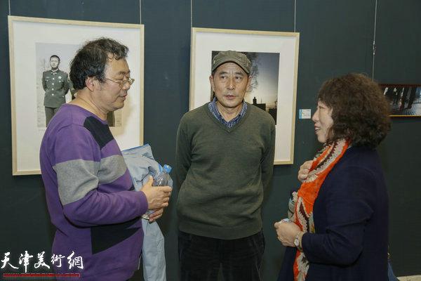 """""""城视""""天津青年当代摄影展11月18日下午在天津美术馆开幕。图为董大明、孙德琪、崔淳在展览现场交流。"""