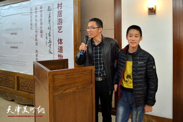 倪金宝与儿子、少年画家倪率在开幕仪式上。