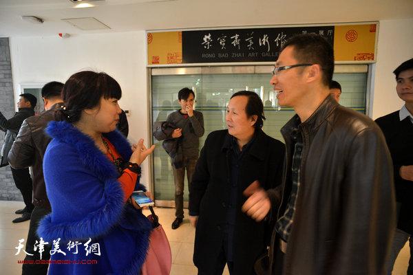 刘方明与来宾在画展现场交流。