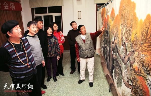 老画家杜明岑向慕名前来观赏画作的客人讲解《丝路胡杨骆驼声》