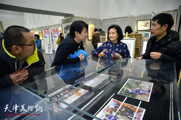 田同芬、张宝欣、李垚在画展现场交谈。