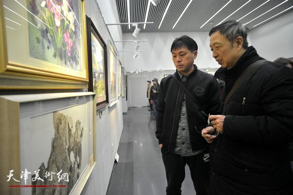 赵军在观赏展出的作品。