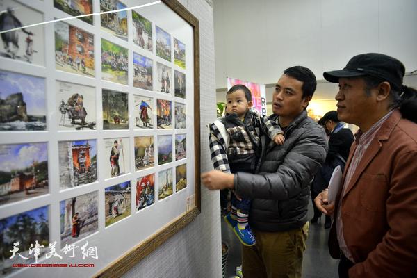 王刚在观赏展出的作品。
