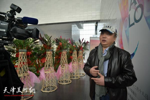 朱志刚在画展现场接受媒体的采访。