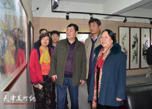李宝春陪同来宾观赏展出的作品。