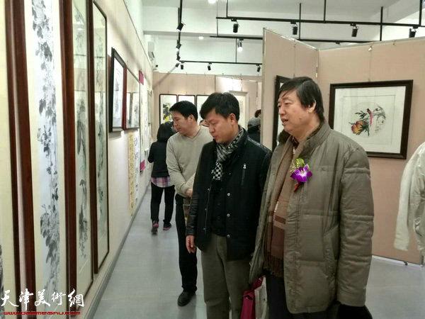 陈元龙、张洪春在观赏展出的作品。