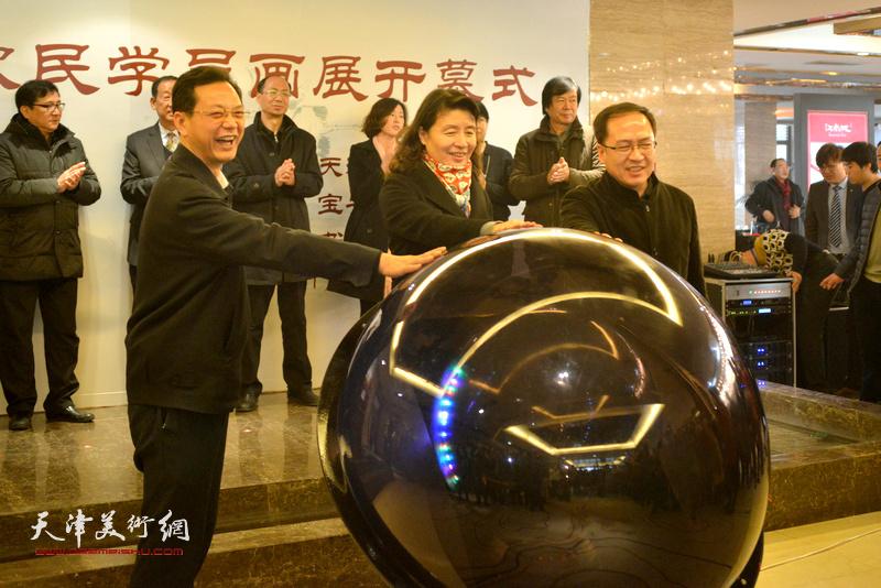 """万镜明、游庆波、张劲按动水晶球为""""迎新春——农民学员画展""""揭幕。"""