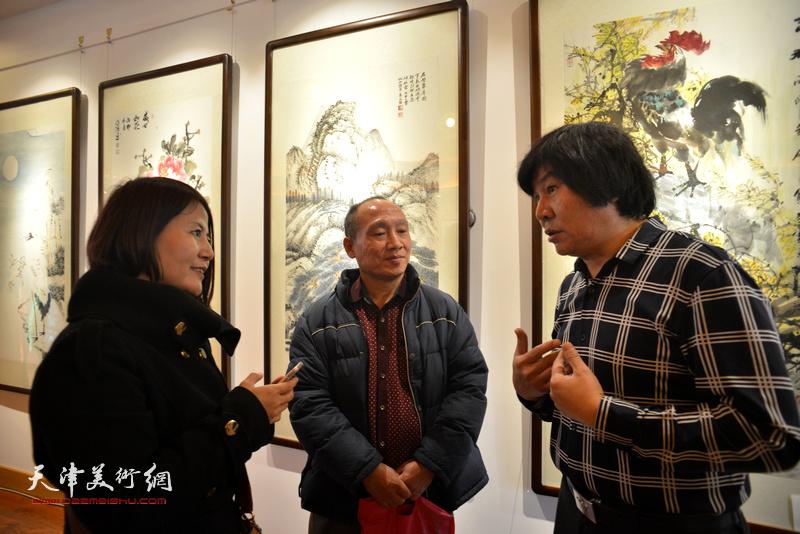 高学年与农民画家在画展现场交流。