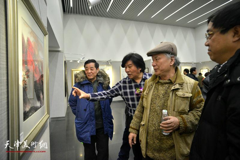李风雨、高学年、刘绍斌观赏展出的画作。