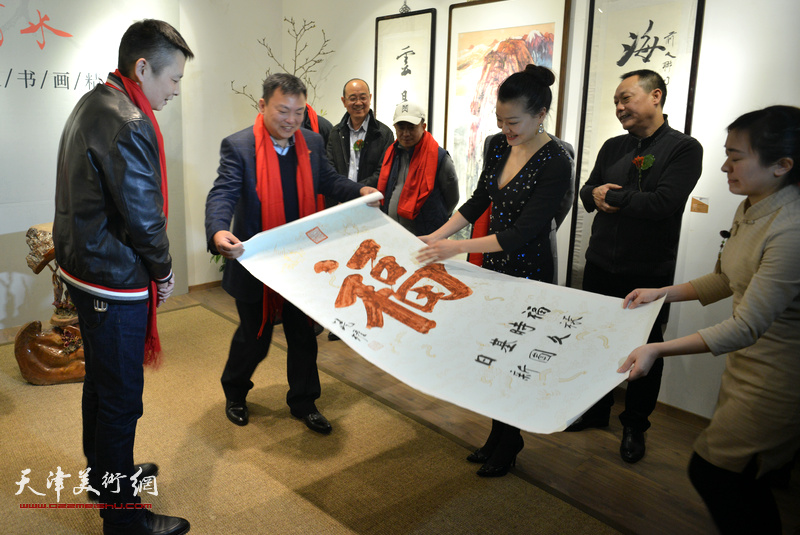 """范权在画展现场为来宾迎春送""""福""""。"""