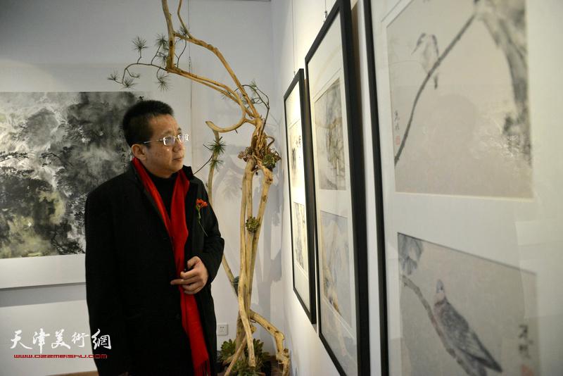 李毅峰在观赏展出的作品。