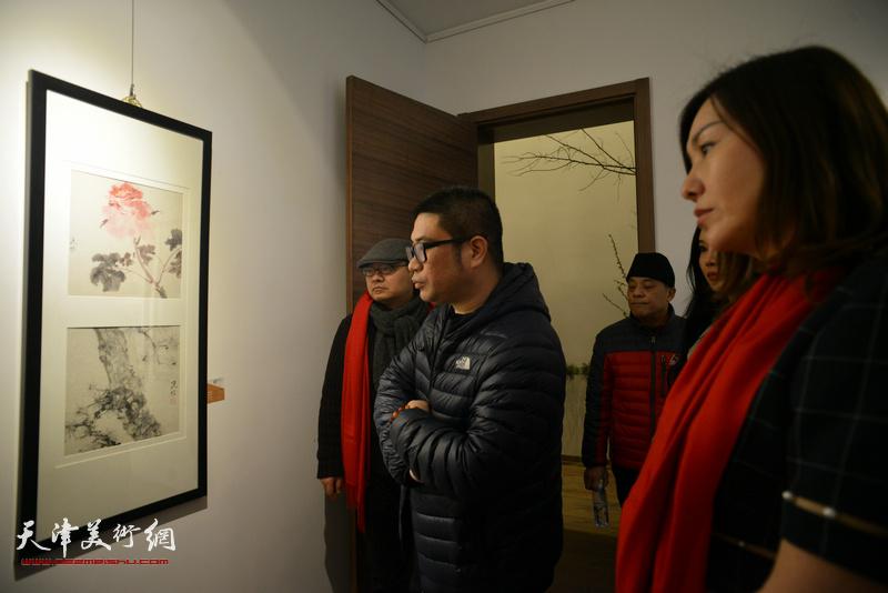 姜立志与来宾观赏展出的画作。