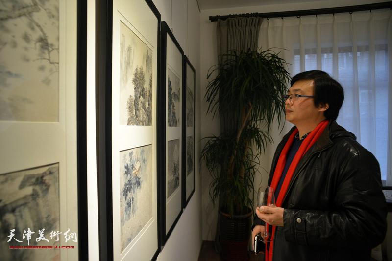 刘波在观赏展出的画作。